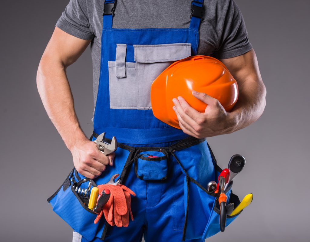 Builder with tools in hand to build on gray background.